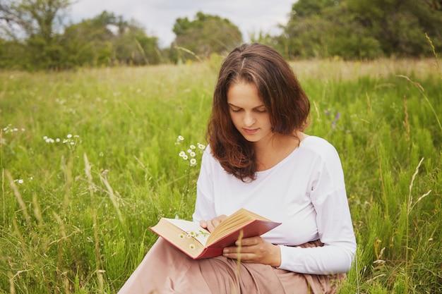 심각한 사랑스러운 젊은 여성의 야외 샷 여름 날씨를 즐기고, 그린 필드에 앉아 큰 관심을 가진 재미있는 책을 읽습니다