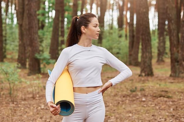 白いスポーツウェアを着た、自信に満ちたスリムな女性の屋外ショット、ヨガマットを手に持ち、目をそらし、腰に手を当てる