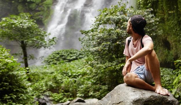 大きな岩の上に裸足で座っていると豪華な滝で彼の肩越しに見ているスタイリッシュな若い白人ハイカーの屋外撮影