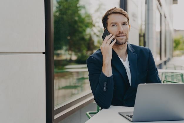 Снимок на открытом воздухе: успешный мужчина-исполнительный работник звонит кому-то через смартфон