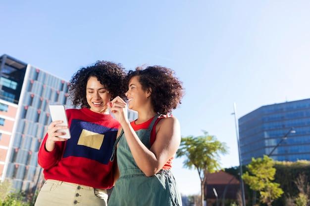 Открытый снимок двух многорасовых молодых женщин, развлекающихся по городу с мобильным телефоном