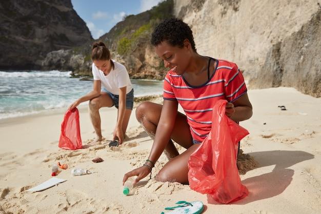 ボランティアの女の子の屋外ショットは、ゴミ袋にゴミを集めます