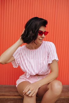 ピンクのストライプのtシャツを着た女性の屋外ショット。木製のベンチでポーズをとるサングラスのブルネットの女性。