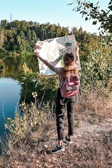 地図を保持しているアクティブな休息を楽しんで旅行に触発されている若いバックパッカーの屋外ショット