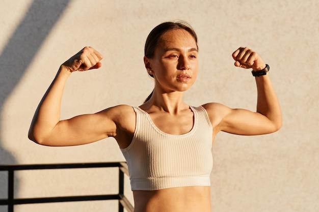 강한 팔 팔뚝, 건강한 몸, 외부의 생산적인 훈련을 보여주는 젊은 여성 운동 선수의 근육 flexing의 야외 촬영, 세련된 흰색 탑을 입고 자신감을 보입니다.