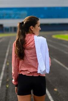 競馬場で走っている若い女性アスリートの屋外ショット。トレーニングセッションの実行中のプロのスポーツウーマン。