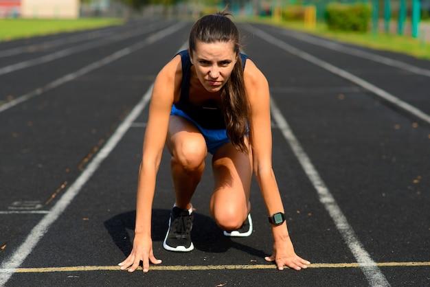 Открытый выстрел спортсмена молодой женщины, бегущего на ипподроме. профессиональная спортсменка во время беговой тренировки.