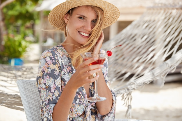 Outdoor shot of pleasant looking female with happy expression, wears summer hat and blouse, holds fresh drink in glass, poses outside against hammock, has party with friends, celebrates birthday