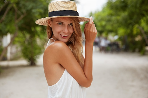 Outdoor shot of pleasant looking female with tanned healthy skin, dressed in white dress and summer hat, poses in park with confident satisfied expression