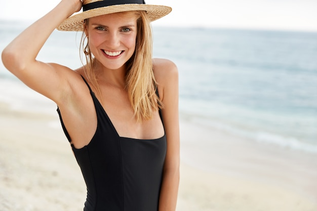 Outdoor shot of pleasant looking young female with cheerful expression, dressed in swimsuit and straw hat, strolls across coastline, has healthy skin and positive expression. summer time concept