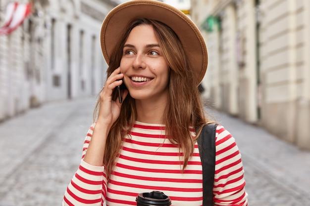 Colpo esterno di felice viaggiatore caucasico parla su smart phone in roaming, gode di tariffe economiche per la comunicazione, si trova sulla strada