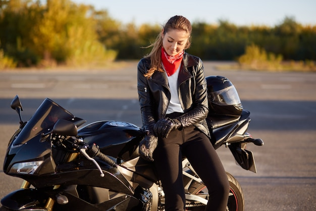 Outdoor shot of pleased female bikes puts on leather gloves, dressed in black clothes, poses on motorbike, prepares for racing or competitions, poses in countryside.