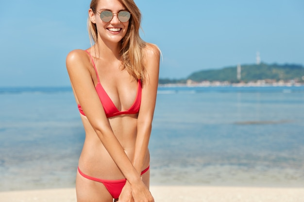 Outdoor shot of pleased young female with tanned skin, slim body, wears red bikini and sunglasses, poses against wonderful ocean view, blue sky, enjoys rest in resort place. people and recreation