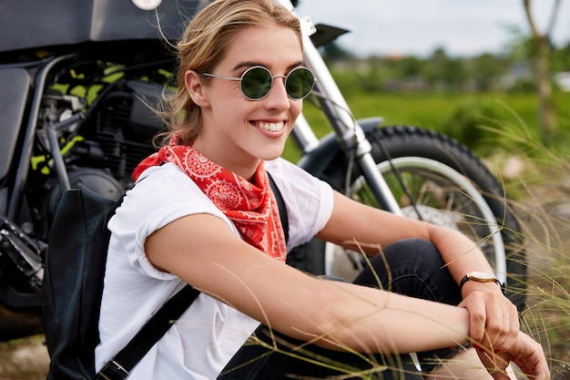Outdoor shot of positive active beautiful woman in trendy shades, wears red bandana on neck, spends free time in open air as rides motorbike, has extremal journey. people, rest and hobby concept