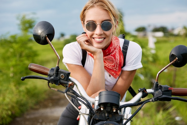 Outdoor shot of positive active female driver sits on fast motorbike, wears fashionable clothing, has break after biker`s competition in countryside. people, motorcycling and lifestyle concept