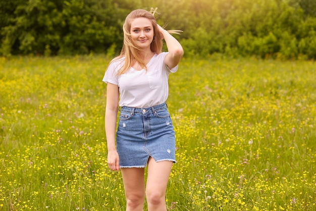 Outdoor shot of pretty blond woman wearing white casual t shirt and denim skirt, posing in meadow, touching her fair hair