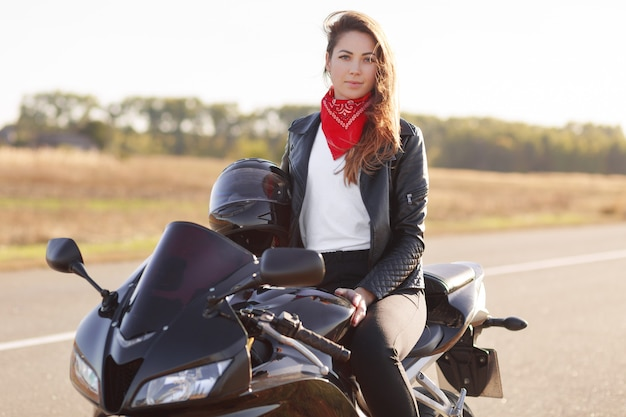 Outdoor shot of pretty woman biker wears red banadana and leahter jacket