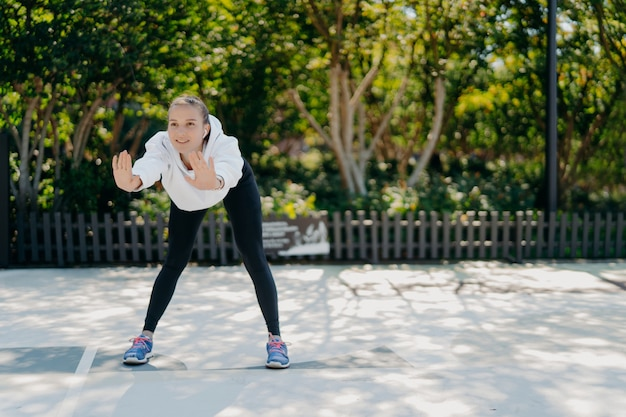 Outdoor shot of satisfied healthy sporty woman leans forward keeps palms raised does exercises in open air trains in park feels good wears sweatshirt leggings and sneakers leads active lifestyle