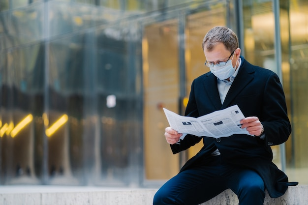 Outdoor shot of serious man boss takes break after walking, reads newspaper, wears spectacles for good vision, medical mask to protect himself from viruses, finds out news about spreading coronavirus