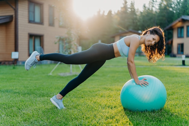 Outdoor shot of slim active sporty woman does fitness exercises with fitball, dressed in active wear, has cheerful expression, poses during sunny day on green grass, being in good physical shape