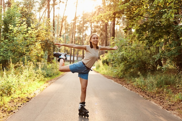 Outdoor shot of slim attractive brunette woman wearing beige t shirt and jeans short rollerblading on one leg and spreading arms aside like flying, healthy lifestyle.