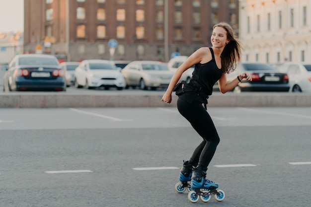 Outdoor shot of slim cheerful woman dressed in active wear looks away leads healthy lifestyle rides on rollers poses on road in urban place feels energized. rollerblading as hobby. recreation