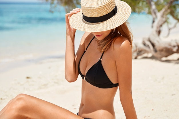 Outdoor shot of slim female model in black bikini and summer hat, sits on sandy beach alone, poses against beautiful ocean view, enjoys summer time. attractive young woman recreats on seashore