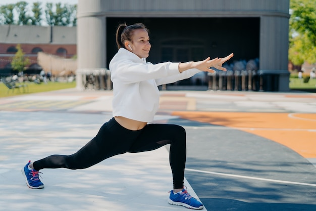 Outdoor shot of slim sporty woman involved in recreation activities stretches arms legs looks into distance wears white hoodie leggings and sportshoes stetches body before run leads healthy lifestyle