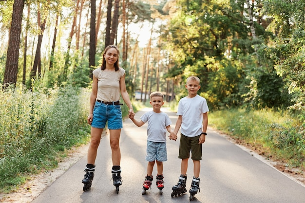 Outdoor shot of smiling attractive female with her little sons standing on road in summer park and holding hands, family rollerblading together, having fun, active pastime.