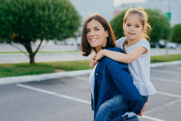 Outdoor shot of smiling woman gives piggyback to her daughter, have walk in open air