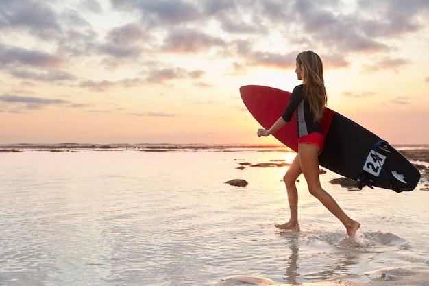 Outdoor shot of sporty surfer runs on ocean water, has slender legs