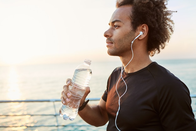 Outdoor shot of stylish dark-skinned male athlete drinking water out of plastic bottle after cardio workout. runner hydrating during training by the sea in the morning sunlight.