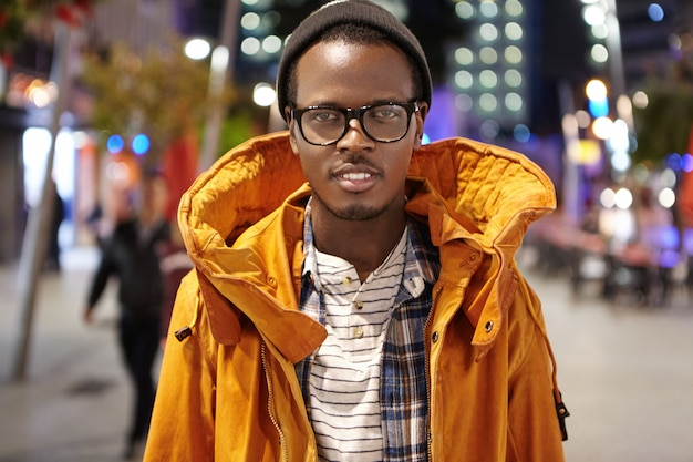 Outdoor shot of stylish dark-skinned tourist in winter coat, hat and glasses walking around night city, hitchhiking across europe, standing in the middle of street and looking with smile