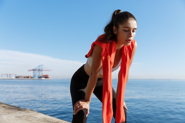 Outdoor shot of tired fitness woman panting and taking a breath after jogging, standing on a pier