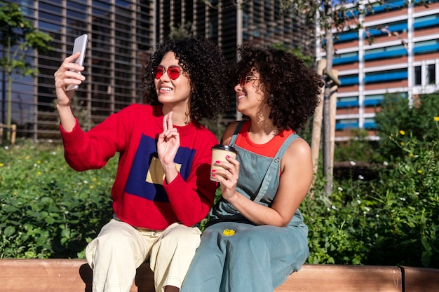 Outdoor shot of two multiracial young female having fun on city with a mobile phone