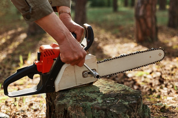 Outdoor shot of unknown person worker fixing chainsaw before or after deforestation