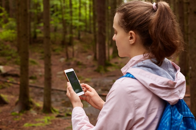 Outdoor shot of woman backpacker get lost and trying to find her way, using online maps in mobile phone in forest, female going for walk in wood