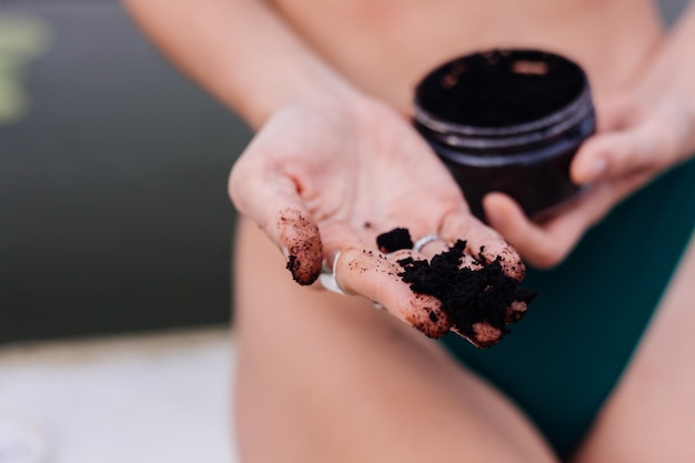 Outdoor shot of woman with coffee body scrub.