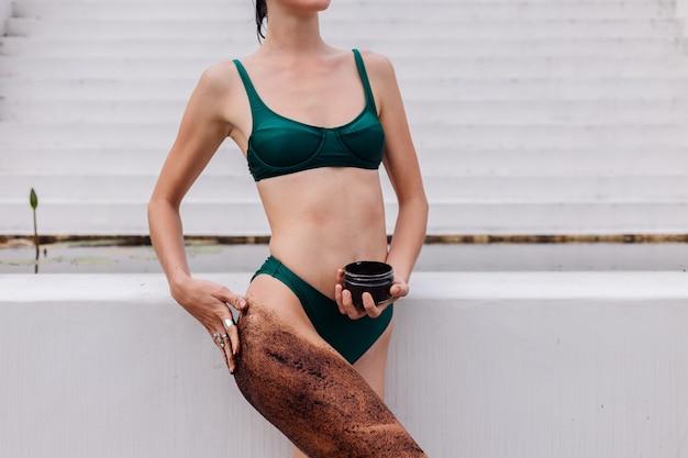 Colpo esterno di donna con scrub corpo caffè.