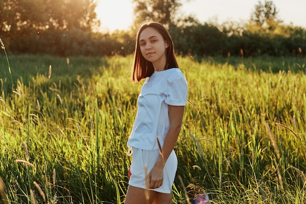 Outdoor shot of young adult beautiful woman wearing white clothes posing in the green meadow, standing and looking at camera, enjoying the beauty and tranquility of nature and the sunset.