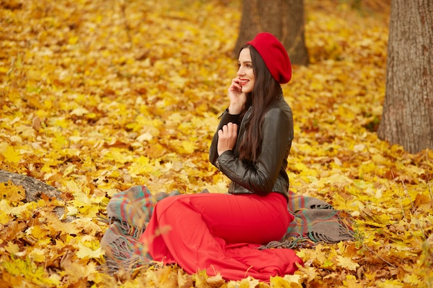 Outdoor shot of young attractive cute girl in red beret, trousers and leather jacket, sitting near trees on yellow leavesin