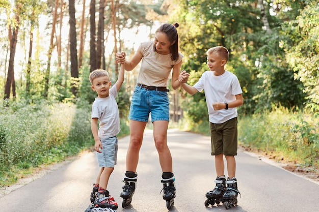 Outdoor shot of young attractive female wearing beige t shirt and jeans short rollerblading with children, mother and kids expressing positive emotions, pastime in summer park.