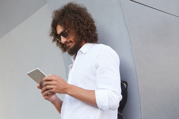 Colpo all'aperto del giovane uomo attraente con la barba, con gli occhiali e una camicia bianca, tenendo il tablet in mano e guardando lo schermo, in posa sul muro grigio