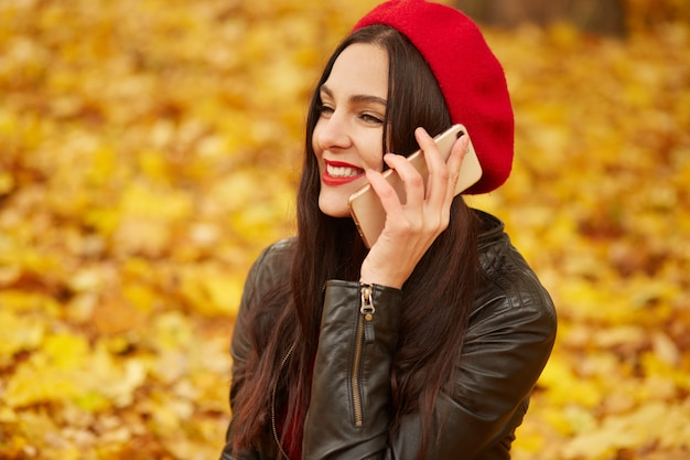 Outdoor shot of young attractive woman in autumn park using her phone for conversation with her boyfriendor hasband, being in good mood