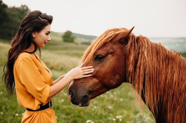 Outdoor shot of a young beautiful woman playing with a horse on a field. charming brunette touching face of a horse.