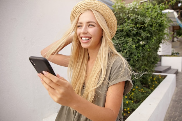 Outdoor shot of young charming woman with long blond hair straightening her straw hat, making selfie with smartphone, being happy and joyful