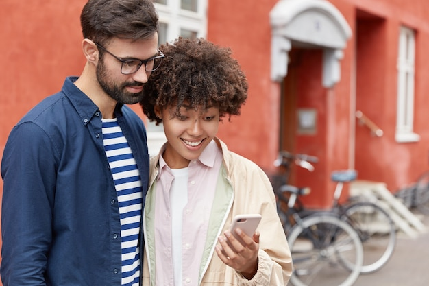 Colpo all'aperto di giovani coppie innamorate hanno passeggiata nel contesto urbano guardando qualcosa su uno smartphone
