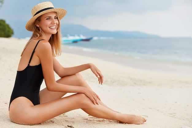 Outdoor shot of young dreamy blonde female in black bikini and straw hat, poses on sea shore, looks at horizon into distance, enjoys marine air, has slim perfect body, enjoys summer vacations.