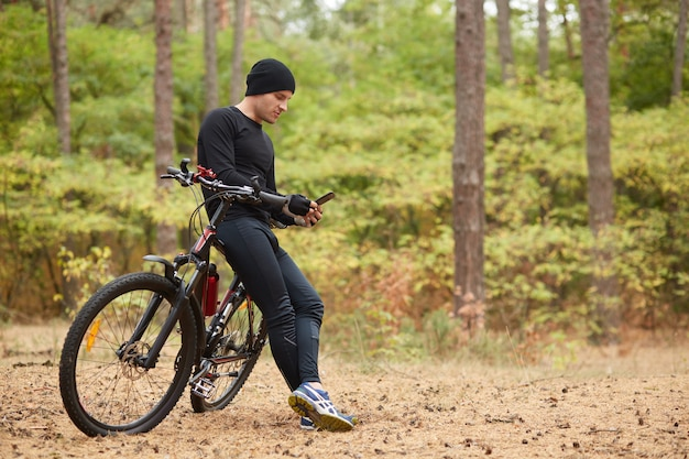Outdoor shot of young european rider standing in forest surrounded with trees, holding mobile phone