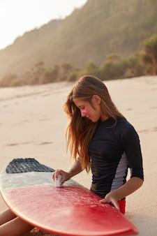 Outdoor shot of young girl waxes surfboard for safe riding waves, dressed in black swimsuit, sits at warm sand, takes care of safety, wears pink zinc around eyes, enjoys freedom. pastime concept